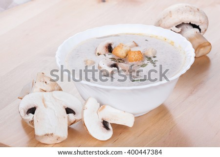 Mushrooms cream soup with agaric, closeup on wooden table - stock photo