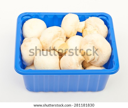 Mushrooms in blue plastic box isolated on white background - stock photo
