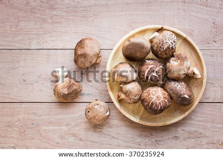 Mushrooms in dish on rustic wooden background  - stock photo