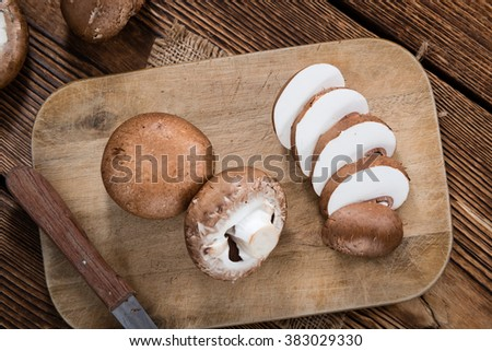 Mushrooms (selective focus) on an old wooden table (close-up shot) - stock photo