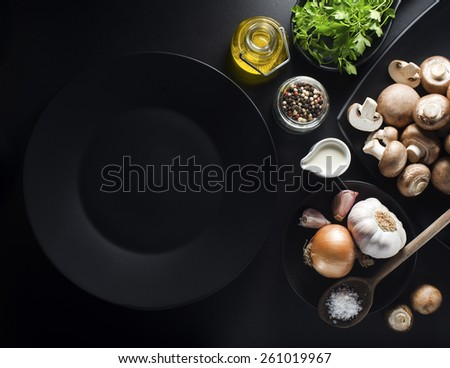 Mushrooms with ingredients on a black background
