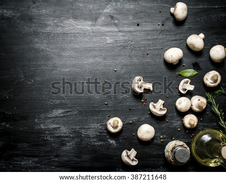 Mushrooms with spices, salt and a bottle of olive oil. On black rustic background. - stock photo
