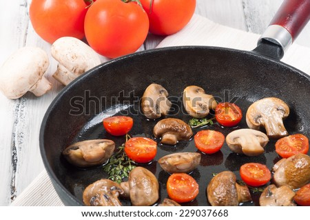 mushrooms with tomatoes on a frying pan on a white wooden background - stock photo