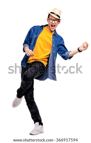 Music and imagination. Happy smiling young man in hat playing air guitar. - stock photo