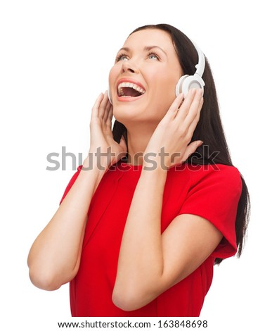 music and technology concept - laughing young woman with headphones - stock photo