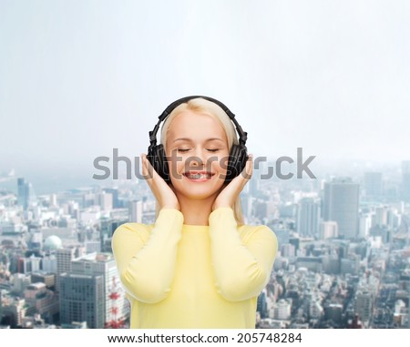 music and technology concept - smiling young woman with closed eyes listening to music with headphones - stock photo