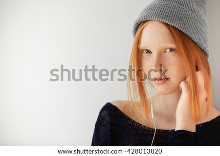 Music and technology concept. Teenage girl listening to audiobook or radio on cell phone with earphones looking and smiling at the camera against white copy space wall for your advertising content  - stock photo
