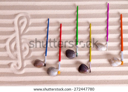 Music at the seaside concept with an artistic arrangement of music notes formed from pebbles and colorful paintbrushes on a background score composed of alternating lines of golden sand - stock photo