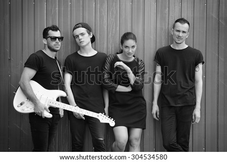 Music band outdoor portrait. Musicians and woman soloist posing outside against grunge fence, black and white. - stock photo