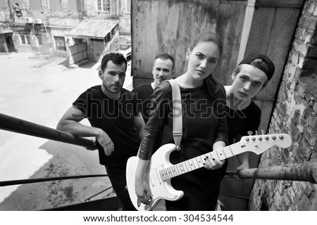 Music band outdoor portrait. Musicians and woman soloist posing outside against grunge yard, black and white. - stock photo