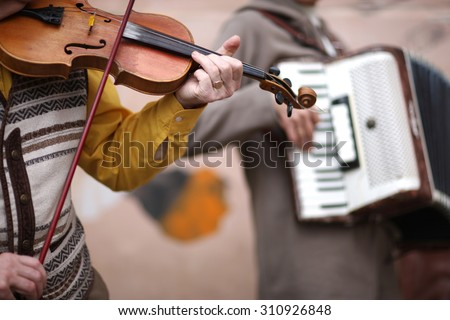 Music band performance; hands of violoncellist in focus - stock photo