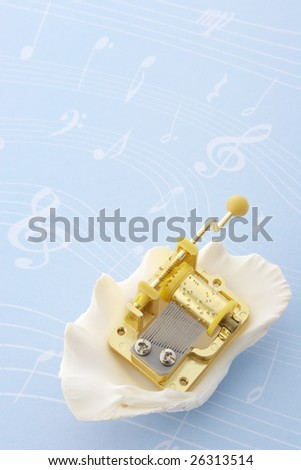 Music box and seashell on music note background - stock photo