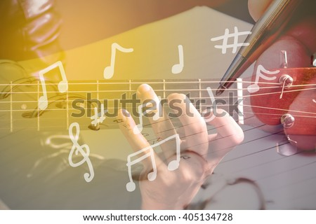 music composition - multiple exposure man playing guitar and writing notes - stock photo