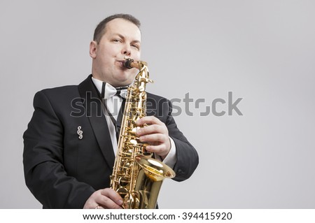 Music Concept and Ideas. Portrait of Caucasian Player in Suit Playing on Saxophone.Horizontal Shot - stock photo