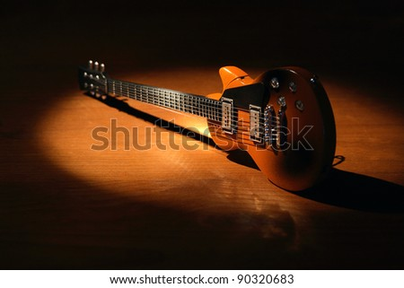 Music concept.Electric guitar on wooden surface under beam of light