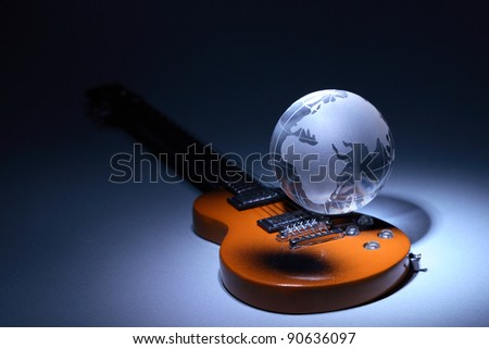 Music concept. Glass globe on electric guitar under beam of light on dark background