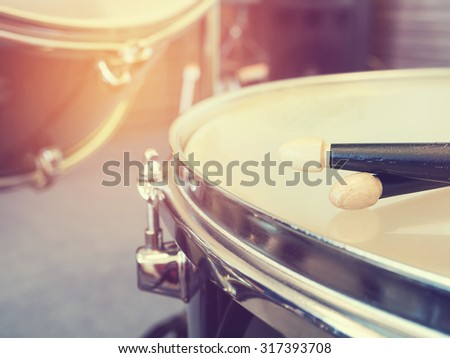 Music concept photo of the pair of wood drumsticks on drum. : Vintage or retro style and filtered process.  - stock photo