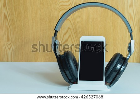 music concept - smartphone and headphones on the wood background,smartphone and headphones close up - stock photo