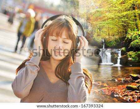 Music concept - Woman listening relating music in the city and teleport to the beautiful forest with waterfall - stock photo