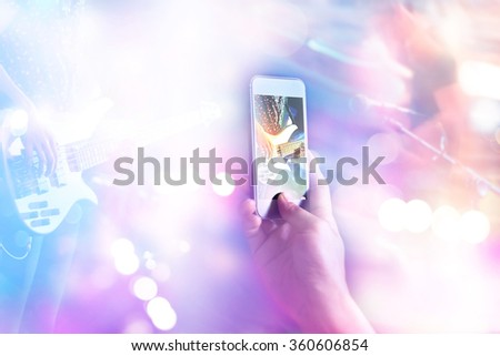 Music fans takes a photo guitarist on stage in concert on smart phone, Soft focus and pastel color tone  - stock photo
