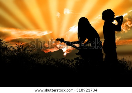 Music for the Earth Rocker and Guitarist are Singing and Playing Rock Music Against the Background of Orange Sky - stock photo