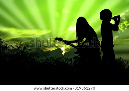 Music for the Earth Rocker and Guitarist are Singing and Playing Rock Music Against the Background of Green Sky - stock photo