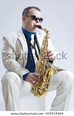 Music Ideas and Concepts. Handsome and Expressive Caucasian Music Player Posing In Sunglasse With Saxophone Against White Background. Vertical Image Orientation - stock photo