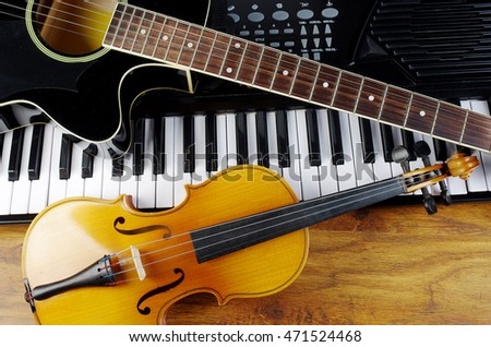 Music instruments.Keyboard synthesizer, violin and acoustic guitar