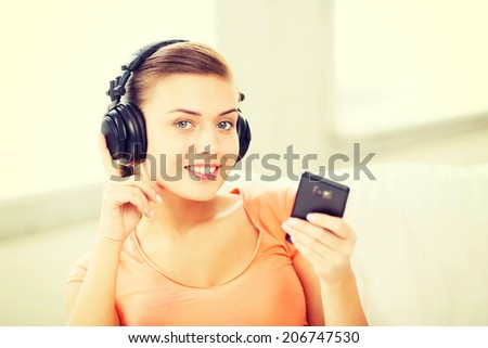music, internet and shopping - woman with headphones and smartphone at home