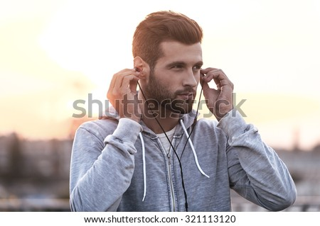 Music is always with me. Confident young man putting headphones into his ears and looking away while standing outdoors - stock photo