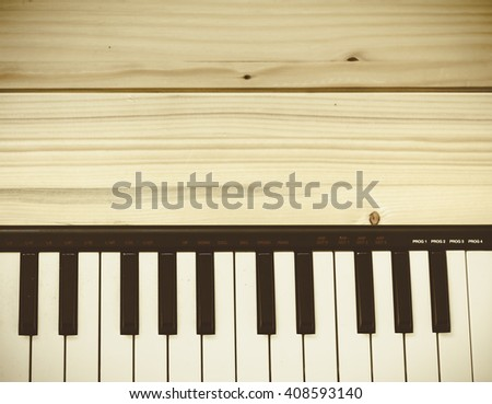Music keyboard shot in flat lay style on a wooden table. View from above - stock photo
