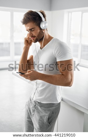 Music Listening. Portrait Of Handsome Muscular Happy Man In Fashion Headphones Using Mobile Phone, Smartphone Indoors. Beautiful Sexy Smiling Male Enjoying Music At Home. Entertainment Concept