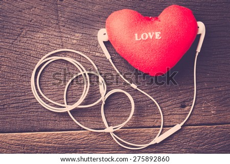 Music lover concept. Red heart and earphone on wood table. Vintage filter. - stock photo