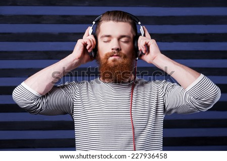 Music lover. Confident young bearded man in headphones standing against stripped background and listening to the music - stock photo