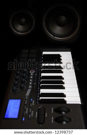 Music midi-keyboard and bass speakers in studio - stock photo