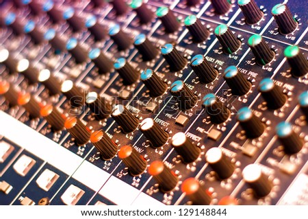 Music mixer with close-up of controls in nightclub with colorful lights - stock photo