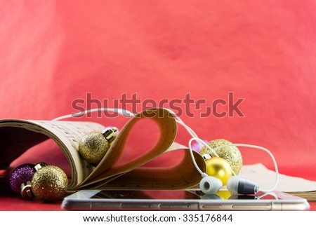 Music notation book with pages shaping heart with earphones and Christmas ornaments - stock photo
