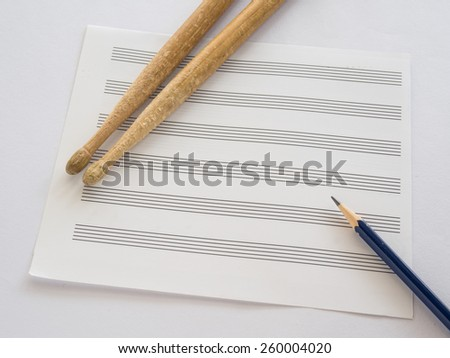 Music note sheet with pencil and drum sticks on white background, Selective focus on Sharpness of pencil - stock photo
