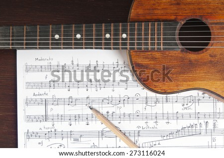 Music notes, vintage guitar and two pencils on table - stock photo