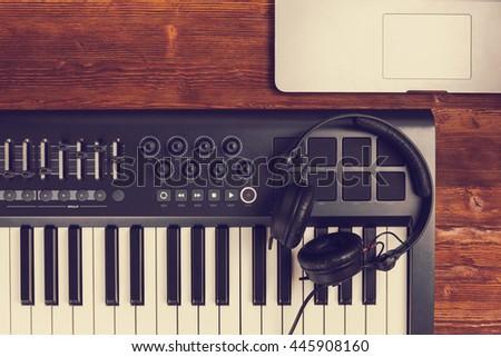 music production set midi piano keyboard retina laptop black dj headphones on wooden desk table. Top view filter - stock photo