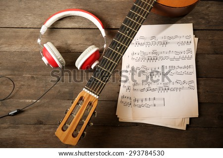 Music recording scene with guitar, music sheets and headphones on wooden table, closeup - stock photo