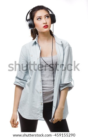 Music. Relaxed woman with big earphones headphones listening to music on mp3 player. Young mixed race Asian Caucasian woman isolated on white background. - stock photo