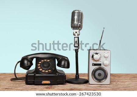 Music. Retro rotary telephone, radio, headphones, microphone on table - stock photo