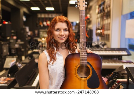 music, sale, people, musical instruments and entertainment concept - smiling female assistant or customer holding acoustic guitar at music store - stock photo