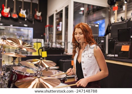 music, sale, people, musical instruments and entertainment concept - smiling female musician playing cymbals at music store - stock photo
