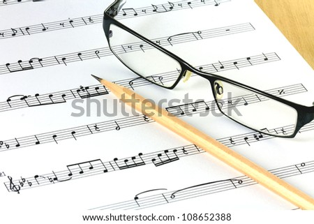 music sheet with pencil and glasses - stock photo