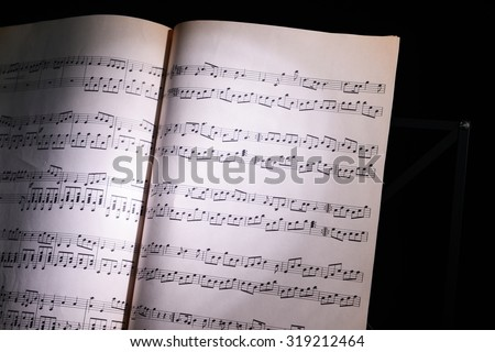 Music sheets in the shadow, closeup - stock photo