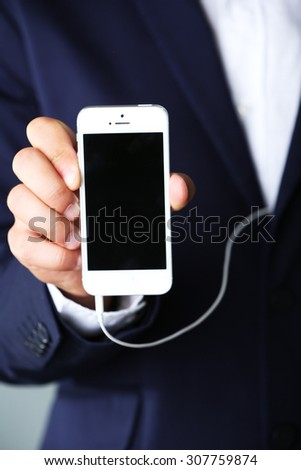 Music smartphone in businessman hand, close-up