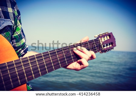 Music sound passion talent relax outdoor leisure concept. Guitarist playing next to sea. Young man with guitar sitting on coast playing instrument.