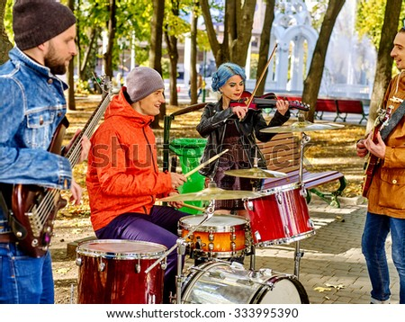 Music street performers with girl violinist on autumn outdoor. - stock photo